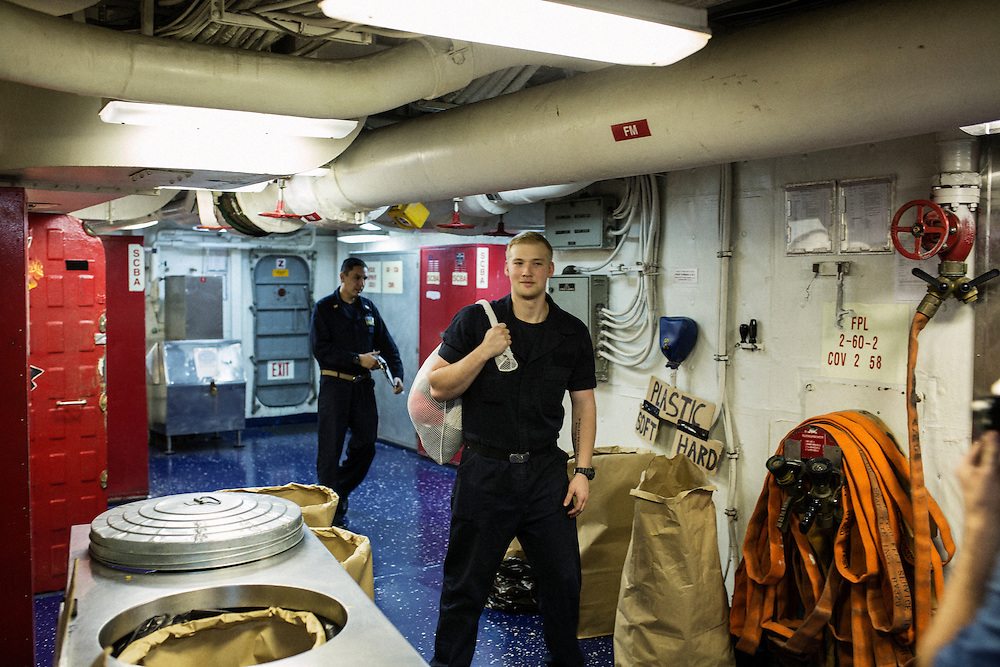 Crew members with laundry<br /> <br /> Aboard the USS Harry S. Truman operating in the Persian Gulf. February 25, 2016.<br /> <br /> Matt Lutton / Boreal Collective for Mashable