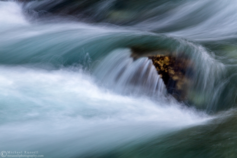 The blue waters of Gold Creek cascade over a rock at Golden Ears Provincial Park in Maple Ridge, British Columbia, Canada
