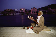 A pilgrim reads holy scriptures on the banks of the Ganges before dawn. Every 12 years, millions of devout Hindus celebrate the month-long festival of Kumbh Mela by bathing in the holy waters of the Ganges at Hardiwar, India. Hundreds of ashrams set up dusty, sprawling camps that stretch for miles. Under the watchful eye of police and lifeguards, the faithful throng to bathe in the river.