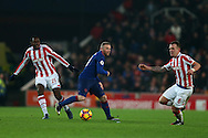 Wayne Rooney of Manchester Utd goes past Giannelli Imbula (l) and Glenn Whelan of Stoke city (r).  Premier league match, Stoke City v Manchester Utd at the Bet365 Stadium in Stoke on Trent, Staffs on Saturday 21st January 2017.<br /> pic by Andrew Orchard, Andrew Orchard sports photography.