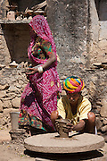 Indian potter in Rajasthani turban works with family at home making clay pots in village of Nimaj, Rajasthan, India