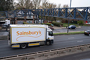 Sainsburys delivery truck passes along the A40 Western Avenue with residential houses either side at Greenford on 4th December 2020 in London, United Kingdom. The A40 is one of the main roads in and out of the capital.
