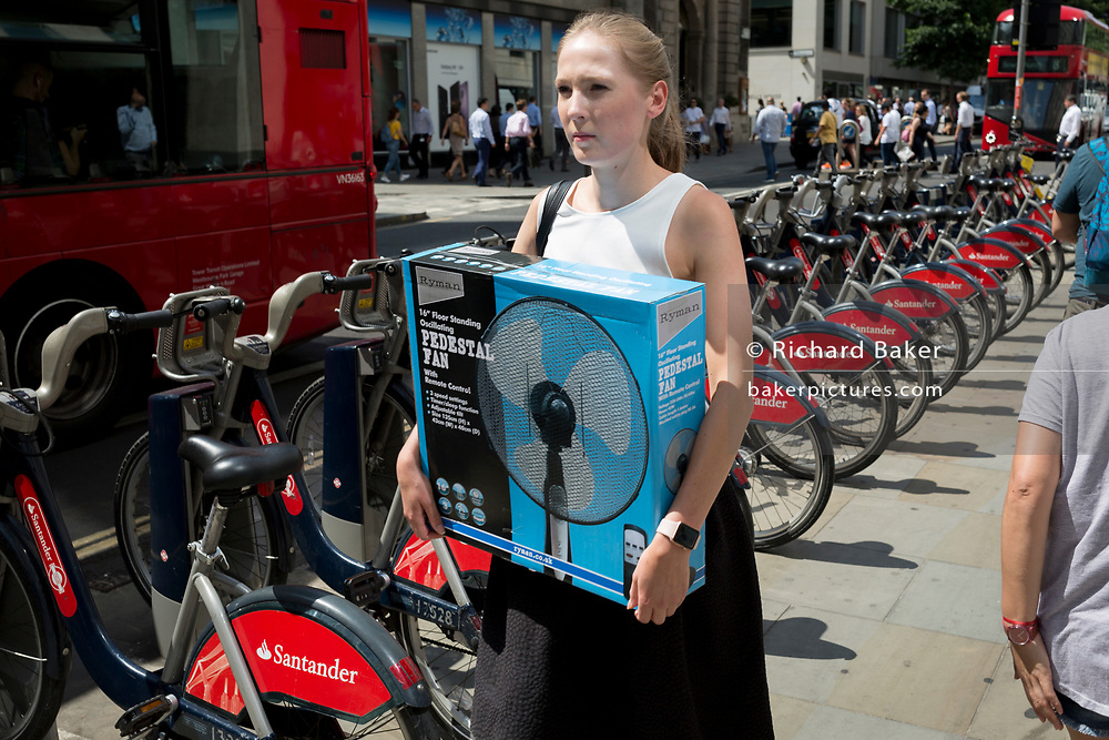 A lady carries a boxed pedestal office fan one of the hottest days of the year, during the 2018 heatwave, in the City of London the capital's financial district, on 24th July 2018, in London, England.