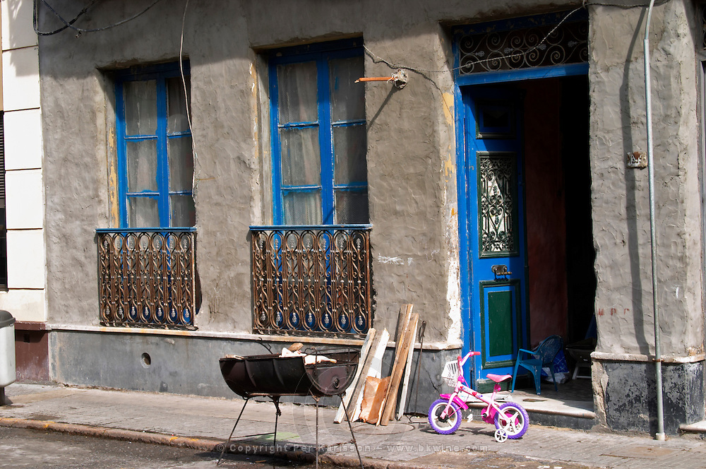 A house in the old town Ciudad Vieja near the harbour at early lunch time, the grill barbecue on the street and prepared with some fire wood, a child's bicycle blue windows and wrought iron railing Montevideo, Uruguay, South America