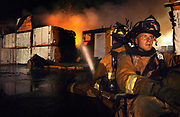 Coeur d'Alene firefighter Keith Benz supports another firefighter as they saturate a section of a fire Thursday July 6, 2006 that completely destroyed Precision Wood Products in Coeur d'Alene, Idaho. Witnesses reported seeing lightning hit the main building shortly before flames began to appear at about 1:30 a.m.