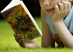 Undated file photo of a child reading a book. Children should be encouraged to read aloud and talk about books with friends to help improve their language skills, it has been suggested.