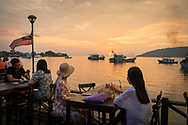 Two women vacationing from Korea enjoy a sunset drink at the waterfront, a public walkway lined with restaurants in Kota Kinabalu, Sabah, Malaysia. (August 14, 2019)