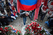 Moscow, Russia, 15/01/2011..A man lays flowers during a rally at the bus stop where Spartak soccer fan Yegor Sviridov was killed in a street fight with a group of men from the southern Caucasus, leading to a nationalist backlash that has spilled into racist violence on the streets of Moscow and other Russian cities. The rally on the 40th day after Sviridov's death was attended by a mixture of local people, football fans and Russian nationalists.