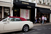 "Rolls Royce car parked outside Chanel Jewellers. Exclusive shops on New Bond Street, Mayfair, central London. It is one of the principal streets in the West End shopping district and is more upmarket. It has been a fashionable shopping street since the 18th century. Technically ""Bond Street"" does not exist: The southern section is known as Old Bond Street, and the northern section, which is rather more than half the total length, is known as New Bond Street. The rich and wealthy shop here mostly for high end fashion and jewellery."