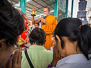 31 AUGUST 2014 - SARIKA, NAKHON NAYOK, THAILAND: A Buddhist monk blesses people during the Ganesh Festival at Shri Utthayan Ganesha Temple in Sarika, Nakhon Nayok. Ganesh Chaturthi, also known as Vinayaka Chaturthi, is a Hindu festival dedicated to Lord Ganesh. It is a 10-day festival marking the birthday of Ganesh, who is widely worshiped for his auspicious beginnings. Ganesh is the patron of arts and sciences, the deity of intellect and wisdom -- identified by his elephant head. The holiday is celebrated for 10 days, in 2014, most Hindu temples will submerge their Ganesh shrines and deities on September 7. Wat Utthaya Ganesh in Nakhon Nayok province, is a Buddhist temple that venerates Ganesh, who is popular with Thai Buddhists. The temple draws both Buddhists and Hindus and celebrates the Ganesh holiday a week ahead of most other places.    PHOTO BY JACK KURTZ
