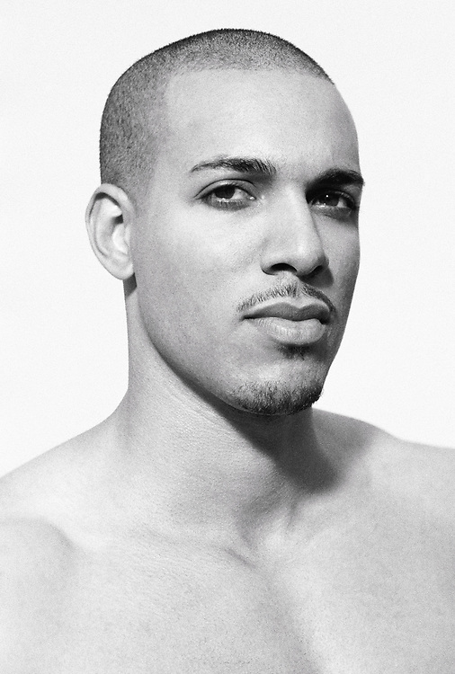 A headshot of a shirtless and handsome young man shot with grainy film on a white background.