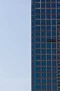 Window cleaners in a cradle high on an office building in Tokyo, Japan. Friday February 3rd 2012