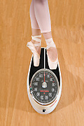 A weightless ballet dancer weighs herself with a scale on a wooden floor