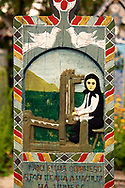 Tombstone of a weaver,   The  Merry Cemetery ( Cimitirul Vesel ),  Săpânţa, Maramares, Northern Transylvania, Romania.  The naive folk art style of the tombstones created by woodcarver  Stan Ioan Pătraş (1909 - 1977) who created in his lifetime over 700 colourfully painted wooden tombstones with small relief portrait carvings of the deceased or with scenes depicting them at work or play or surprisingly showing the violent accident that killed them. Each tombstone has an inscription about the person, sometimes a light hearted  limerick in Romanian. .<br /> <br /> Visit our ROMANIA HISTORIC PLACXES PHOTO COLLECTIONS for more photos to download or buy as wall art prints https://funkystock.photoshelter.com/gallery-collection/Pictures-Images-of-Romania-Photos-of-Romanian-Historic-Landmark-Sites/C00001TITiQwAdS8