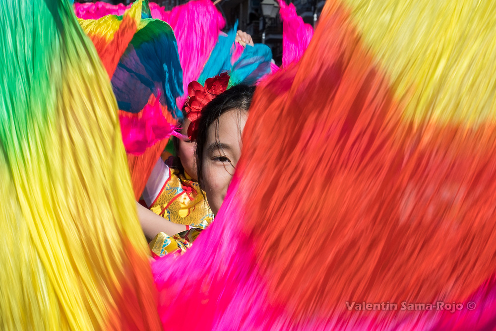 Madrid, Spain. 18th February, 2018. Face of a girl dancing with color fabrics during the Chinese New Year parade in Madrid. © Valentin Sama-Rojo