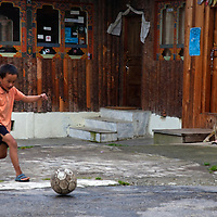 Asia, Bhutan, Bumthang. Kid plays with soccer ball in Bhutan.