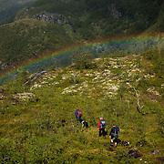 Trekkers walking under a rainbow in the Skarvheimen nature reserve in Norway