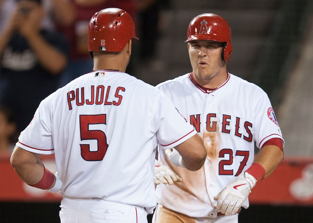 The Angels' Mike Trout reacts after Albert Pujols' second three-run home run of the game in the fifth inning against the Texas Rangers at Angel Stadium on Tuesday.<br /> <br /> ///ADDITIONAL INFO:   <br /> <br /> angels.0720.kjs  ---  Photo by KEVIN SULLIVAN / Orange County Register  -- 7/19/16<br /> <br /> The Los Angeles Angels take on the Texas Rangers at Angel Stadium.
