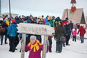 A woman poses beneath the sign marking the old hospital stairs, site of SolFest in Longyearbyen, Svalbard. The festival marks the official arrival of the sun to the town – by tradition, to the old hospital steps (sykehustrappa).