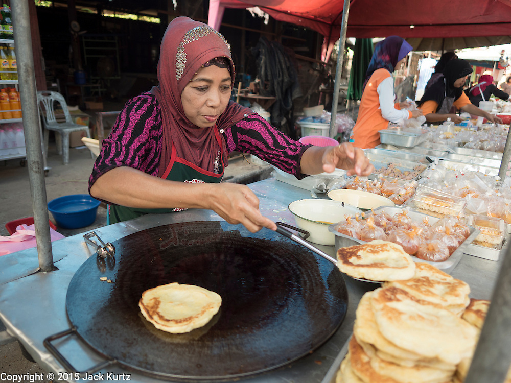 18 JUNE 2015 - PATTANI, PATTANI, THAILAND:   A woman sells roti, a type of fried flat bread, in the Pattani Ramadan Bazaar. People come to the street food market late in the day to buy meals for the evening Iftar meal, which breaks the day long fast. Ramadan is the ninth month of the Islamic calendar, and is observed by Muslims worldwide as a month of fasting to commemorate the first revelation of the Quran to Muhammad according to Islamic belief. This annual observance is regarded as one of the Five Pillars of Islam. Islam is the second largest religion in Thailand. Pattani, along with Narathiwat and Yala provinces, all on the Malaysian border, have a Muslim majority.       PHOTO BY JACK KURTZ