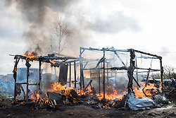 Licensed to London News Pictures. Calais, France. 03/03/16.  The carcas of a shelter that burnt down amid the eviction. French authorities are clearing the southern half of the Calais 'Jungle' camp, which charities estimate to contain 3,500 people.. Photo credit : Rob Pinney/LNP