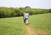 Two people walking on path across a field, St Keverne, Cornwall, England, UK
