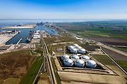 Nederland, Groningen, Eemshaven, 01-05-2013; Overzicht Eemshaven met Vopak Terminal Eemshaven met olieopslag in tanks. In de achtergrond verschillende energiecentrales, midden in beeld opslag van onderdelen voor de assemblage (samen te stellen) van offshore windturbines zoals  masten, de turbine en de wieken, z.g.  superwindmolens met een enorm vermogen ook wel mega-windturbines. .Vopak Terminal in the Port of Eemshaven, oil storage in oil tanks, middle photo storage of parts for the assembly of offshore wind turbines such as masts, the turbine and blades (sails). A blue Wadden Sea.  .luchtfoto (toeslag op standard tarieven).aerial photo (additional fee required).copyright foto/photo Siebe Swart