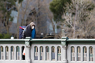 A hooded man wearing a mask and a large bag on his back, walks across the Princes Bridge. (Photo by Dave Hewison/Speed Media)