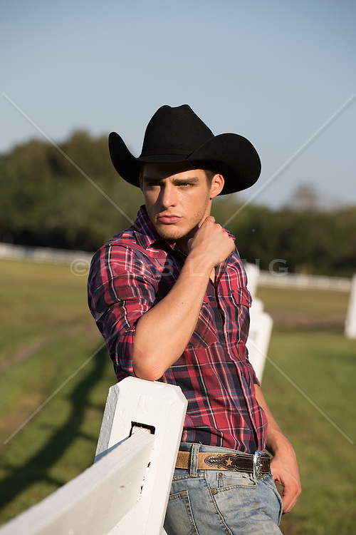 rugged All American cowboy leaning on a beautiful wooden fence
