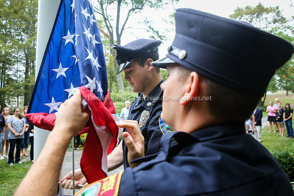 (9/11/16, SUDBURY, MA) Firefighter Matt MacDonald, right, and Officer Owen Boyle, raise the American Flag during a memorial ceremony at the Memorial Garden in Heritage Park in Sudbury on Sunday. The attacks on 9/11 took the lives of Sudbury residents Geoffrey Cloud, Cora Hidalgo Holland, and Peter Morgan Goodrich. Daily News and Wicked Local Photo/Dan Holmes