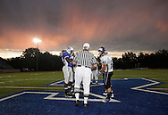 Captains from Middletown, left, and Monroe-Woodbury meet with officials on the field before the start of their football game at Middletown's Faller Field on Friday, Sept. 3, 2010.