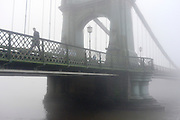 © Licensed to London News Pictures. 11/12/2013. London, UK. A man walks across a fog covered Hammersmith Bridge.  Fog along the banks of the River Thames in Hammesmith, West London this morning 11th December 2013 . Photo credit : Stephen Simpson/LNP
