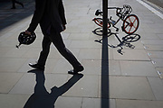 The fallen shape of a Mobike and its twisted shadow on the ground near Broadgate, on 17th April 2018, in the City of London, England.