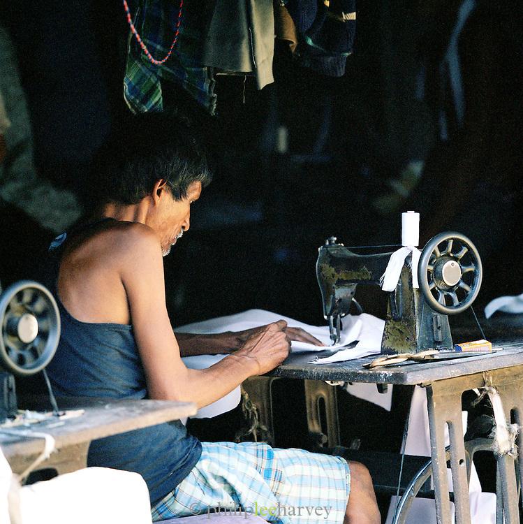 Man sewing in market stall, Lucknow, Uttar Pradesh, India.
