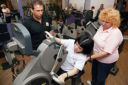 Access to services, Fitness instructor and carer with disabled girl in the gym; using Ergometer,