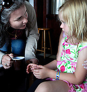 French woman holding cup of coffee speaking directly to her young female Polish cousin age 35 and 4. Zawady Central Poland