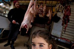A young Palestinian girl plays outside her family's butcher shop in the Sabra and Shatila neighborhood in Beirut, Lebanon, March 17, 2006. On Sept. 16, 1982, what is considered one of the worst atrocities of the civil war happened in this refugee camp. Militants from the Lebanese Forces, with help from the Israeli military, closed off the Palestinian quarters of the Sabra and Shatila refugee camps and killed up to 2,000 Palestinian civilians over three days. Today there are 12 official refugee camps scattered across Lebanon housing some 400,000 Palestinian refugees.