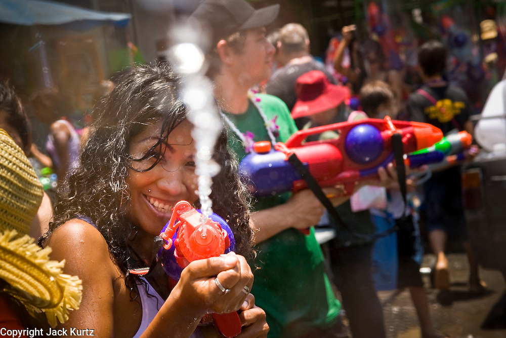 """Apr. 13, 2010 - Bangkok, Thailand: Thais and tourists get into water fights during Songkran festivities on a soi off of Sukhumvit Rd in Bangkok Tuesday. Songkran is the Thai New Year's holiday, celebrated from April 13 - 15. This year's official celebrations have been cancelled because of the Red Shirt protests but Thais are still marking the holiday. It's one of the most popular holidays in Thailand. Songkran originally was celebrated only in the north of Thailand, and was adapted from the Indian Holi festival. Except the Thais throw water instead of colored powder. The throwing of water originated as a way to pay respect to people, by capturing the water after it had been poured over the Buddhas for cleansing and then using this """"blessed"""" water to give good fortune to elders and family by gently pouring it on the shoulder. Among young people the holiday evolved to include dousing strangers with water to relieve the heat, since April is the hottest month in Thailand (temperatures can rise to over 100°F or 40°C on some days). This has further evolved into water fights and splashing water over people riding in vehicles. The water is meant as a symbol of washing all of the bad away and is sometimes filled with fragrant herbs when celebrated in the traditional manner. Photo by Jack Kurtz"""