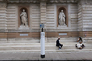 With a further 89 UK covid victims in the last 24hrs, bringing the total victims to 43,995 during the Coronavirus pandemic, pubs, restaurants, hairdressers and some art galleries such as here, at the Royal Academy, will open again on Saturday 4th July. Two Londoners sit and chat separated by 2 metres, according to the governments rules, as shown on many social distance notices around the capital, on 2nd July 2020, in London, England.