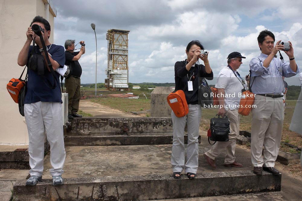 Standing on weathered concrete at an old launchpad from a bygone age, space tourists stop to photograph the current Ariane 5 launchpad while on a tour of the European Space Agency at Kourou, French Guiana. They are mostly Japanese, representing their B-SAT communications satellite which is to be sent into orbit later that night alongside a US-made Hughes Corporation and Lockheed Martin technology. An American NASA space technician walks past the four Japanese as they hold cameras that record their souvenirs of a memorable day at this space facility deep in the South American rainforest. The orange bags carried by all are gas masks. Should the out of sight rocket booster explode or leak liguid propellant, dangerous fumes might overcome the visitors.