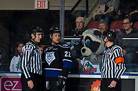 KELOWNA, CANADA - JANUARY 25:  Tanner Sidaway #22 of the Victoria Royals stands with refers Jeff Ingram and linesman Josh Albinati as Rocky Raccoon, the mascot, mocks from behind the glass on January 25, 2019 at Prospera Place in Kelowna, British Columbia, Canada.  (Photo by Marissa Baecker/Shoot the Breeze)