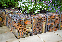 Wire gabions filled with recycled terracotta tiles and stones used to form raised bed and seating. The Real Rubbish Garden. Design: Claire Whitehouse - Chelsea 2005