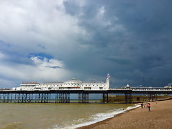 © Licensed to London News Pictures. 25/06/2016. Brighton, UK. Dark rain clouds gather over the pier at Brighton's Promenade on a damp and cold summers day. Photo credit: Hugo Michiels/LNP