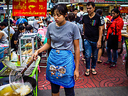 """18 MAY 2017 - BANGKOK, THAILAND: A woman gets ready to make deep fried appetizers at a street food stall in Bangkok's Chinatown. City officials in Bangkok have taken steps to rein in street food vendors. The steps were originally reported as a """"ban"""" on street food, but after an uproar in local and international news outlets, city officials said street food vendors wouldn't be banned but would be regulated, undergo health inspections and be restricted to certain hours on major streets. On Yaowarat Road, in the heart of Bangkok's touristy Chinatown, the city has closed some traffic lanes to facilitate the vendors. But in other parts of the city, the vendors have been moved off of major streets and sidewalks.      PHOTO BY JACK KURTZ"""