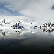 The icy and rocky landscape of Neko Harbour on the Antarctic Peninsula reflected on glassy mirror-like calm waters.