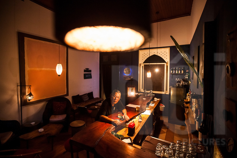 Journalist, artist, and bar owner Nguyen Qui Duc sits at his bar, Tadioto, in Hanoi, Vietnam, Southeast Asia