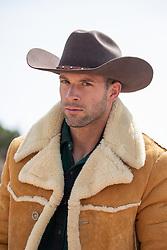 Portrait of a rugged good looking cowboy in a sheepskin coat