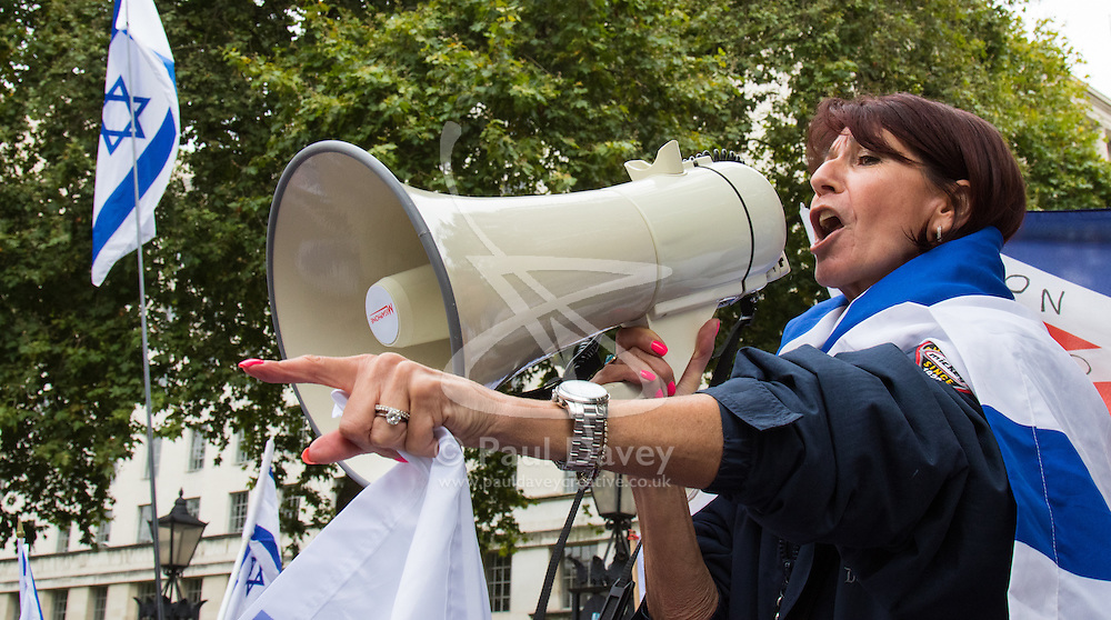 Whitehall, London, September 9th 2015.  A woman cloaked in an Israeli flag uses a loudhailer as pro Palestinian and Israeli counter-protesters clash in Whitehall as the Palestinian Solidarity campaign demands the arrest of Israel's PM Benyamin Netanyahu for war crimes in the 2014 war with Palestinians in Gaza.  // Contact: paul@pauldaveycreative.co.uk Mobile 07966 016 296