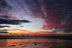 A colourful sky at dawn with cargo ships in the distance seen from Tynemouth beach.