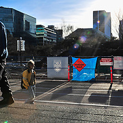 A masked man walks along the steps of the Vancouver Art Gallery (Robson Street side).